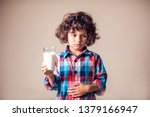 Small photo of Kid boy with stomach pain holding a glass of milk. Dairy Intolerant person. Lactose intolerance, health care concept.