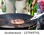 Friends having beers by the bbq at a party, with meat smoking on the hot grill, hands only - stock photo