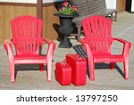 Two red chairs and two red suitcases - stock photo