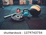 Small photo of Disassembled barbell, medicine ball, kettlebell, dumbbell lying on floor in gym. Sports equipment for workout with free weight. Functional training