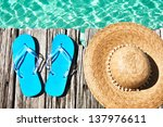 slippers and hat at jetty by... | Shutterstock . vector #137976611