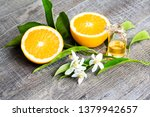 Small photo of Juicy Orange cut in two parts and neroli, flowers of orange tree, on rustic wood background. The Orange blossom is the fragrant flower of the Citrus is used in perfume and tea, aphrodisiac.