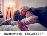 Stock photo hugging sick girl grey haired loving and caring granny hugging her sick cute girl falling asleep 1381065347