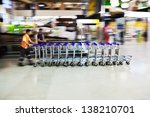 motion blur picture of worker with trolley cars at an airport - stock photo