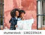 afro young mother using a map...   Shutterstock . vector #1382235614