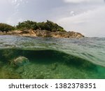 photo taken in the crystal clear waters of the island of Ksamil Albania showing a fish underwater and the island on the other half of the picture