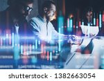 Business team working together at night office.Technical price graph and indicator, red and green candlestick chart and stock trading computer screen background. Double exposure. - stock photo