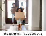 Small photo of Happy small African American girl holding cardboard box run into new house, young black family moving into bought apartment, excited daughter carry personal belongings to home. Relocation concept