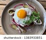 Labskaus traditional Hamburg dish with fried egg, matjes and pickled cucumbers on the plate close up