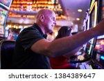 elderly tourist playing slot... | Shutterstock . vector #1384389647