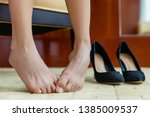 Stock photo tired woman removing high heels off feet shoe pain concept closeup of barefoot lady with painful 1385009537