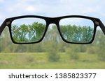 black glasses in front of green ...   Shutterstock . vector #1385823377