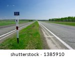 straight road between agricultural fields - stock photo