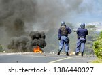 Small photo of standing among debris and rocks thrown by violent protesters, two policemen watch a raging fire, during violent protests in South Africa.