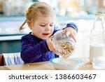 adorable toddler girl eating... | Shutterstock . vector #1386603467