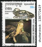 Small photo of CAMBODIA - CIRCA 2000: A stamp printed in Cambodia shows an Amboina Box Turtle or Southeast Asian Box Turtle, Cuora amboinensis, swimming. Turtle shaped carved stone jar, circa 2000.