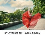 Romantic portrait of the woman in airy red dress dancing on the boulevard - stock photo