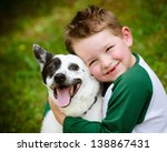 Stock photo child lovingly embraces his pet dog a blue heeler 138867431