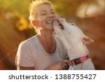 Stock photo smiling woman with white dogo argentino dog puppy trying to pose but the dog is licking and 1388755427