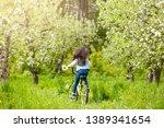 little girl rides a bike... | Shutterstock . vector #1389341654