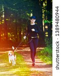 Stock photo girl running with dog outdoors in nature on a path in forest sunny day countryside copy space for 1389480944