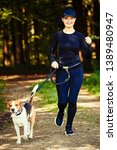 Stock photo girl running with dog outdoors in nature on a path in forest sunny day countryside copy space for 1389480947