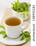 Small photo of Lemon verbena Herbal Tea in a cup. Aloysia citriodora. Naturopathy. White Background. Focus on foreground.