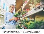 young woman choosing plant in... | Shutterstock . vector #1389823064
