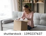 Happy woman sitting on couch at home opening carton box received parcel package from relatives or shopper make order internet website satisfied client, easy and fast service commerce delivery concept