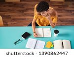 Stock photo high angle view of african girl studying in library young brazilian student copying notes from 1390862447