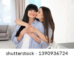 young woman kissing her mature... | Shutterstock . vector #1390936724