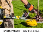 Caucasian Gardener with Gasoline Brush Cutter and String Trimmer on His Shoulder. Trimming Garden Grass. Landscape Maintenance. - stock photo