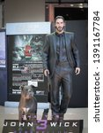Small photo of Bangkok, Thailand - May 4, 2019 : A photo of John Wick and his pitbull dog, partner in crime. Life size figure of John Wick is located in front of theatre to promote movei John Wick 3 parabellum.