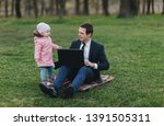 A serious businessman in a suit sits in a park on green grass and works on a laptop, a small child runs alongside and distracts. Computer, lifestyle, work. Father and daughter, business.