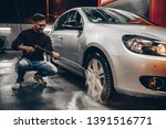 Young man washing his car in the evening at car wash station using high pressure water. - stock photo