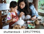 mother and daughter painting... | Shutterstock . vector #1391779901