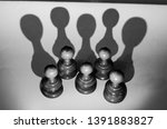 Chess pawns arranged so their shadows create the chess queen symbol. Concept for strength in numbers , power of unity. Grayscale
