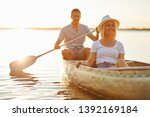 Smiling young couple enjoying a day paddling a canoe together on a lake on a late summer afternoon