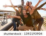 Small photo of Portrait Of Young Friends Outdoors Posing On Gangway Together