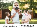 happy playful family outdoors.... | Shutterstock . vector #1392370967