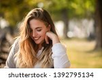 Stock photo smiling shy teenage girl with her head down 1392795134