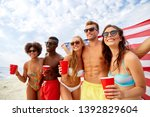 summer, holidays and people concept - group of happy friends with flag and non-alcoholic drinks celebrating american independence day and party on beach