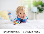 child playing in bed in white... | Shutterstock . vector #1393257557