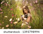 Stock photo girl holding a kitten in the flowers of cosmos 1393798994