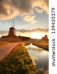 Stock photo traditional dutch windmills with canal against sunset in amsterdam area holland 139435379