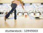 Woman bowling, rear view