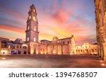 Panorama of Piazza del Duomo square , Campanile tower and Virgin Mary Cathedral ( Basilica di Santa Maria Assunta in Cielo ) , Caritas Diocesana in Lecce - Puglia, Italy. Baroque city of Apulia sunset