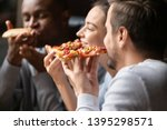 Stock photo close up happy diverse friends eating pizza in cafe together biting slices multiracial people 1395298571