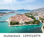 Aerial view of touristic old Trogir, historic town on a small island and harbour on the Adriatic coast in Split-Dalmatia County, Croatia. Flock of gulls or other black birds flying around.