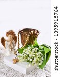 Small photo of First communion or baptism composition with prayer book, rosary, angel and flowers on white background